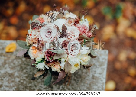 Bridal  Wedding Bouquet on Autumn foliage background, outdoor - stock photo