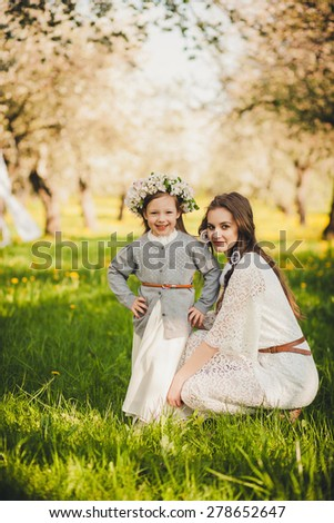 Bride and a little girl with a wreath in the park. - stock photo