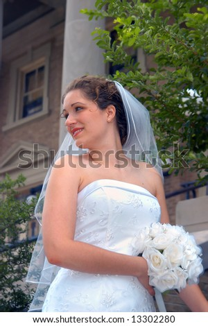 Bride and bouquet pose outside Church building.  White roses, veil, and strapless gown. - stock photo