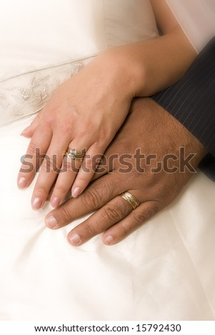 Bride and bridegroom hands over wedding dress (wedding rings) - stock photo
