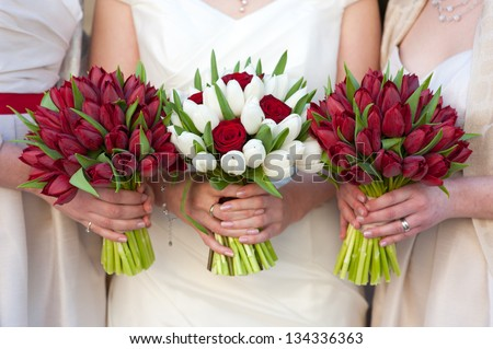 bride and bridesmaids holding red tulip wedding bouquets - stock photo