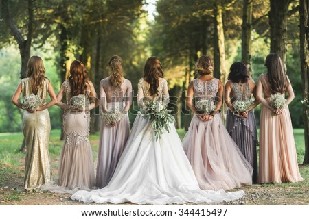 Bride and bridesmaids near trees - stock photo