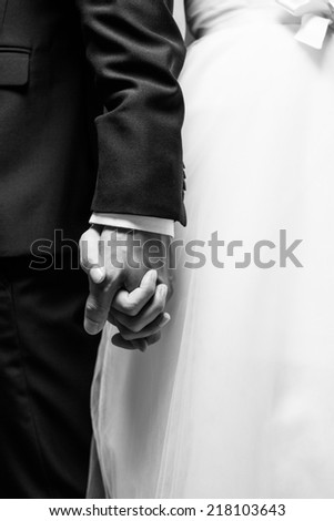 Bride and groom are holding each other's hands at wedding in black and white picture - stock photo