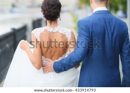 Bride and Groom are walking away in garden. - stock photo