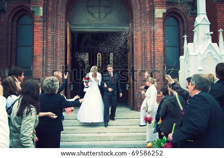 Bride and Groom at church door with rice confetti being thrown - stock photo