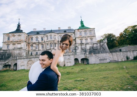 Bride and groom at wedding Day walking Outdoors on castle territory. Bridal couple, Newlywed woman and man embracing with love. People happy and smile - stock photo