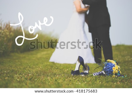 Bride and groom blurred in background. Shoes and flowers in focus with copy space on left. In vintage tone with Love handwritten text on the left. - stock photo