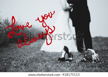 """Bride and groom blurred in background. Shoes and flowers in focus with copy space on left. In black and white with red text that reads """"Love you always"""". - stock photo"""