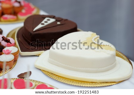 Bride and groom cakes made of white and milk chocolate - stock photo