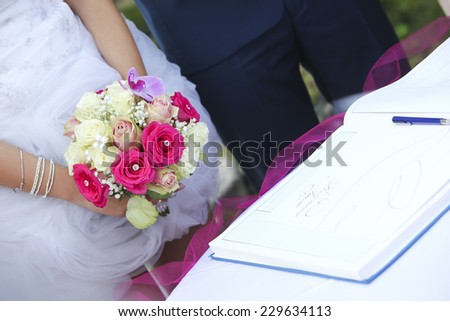 Bride and groom close together, bride holding bouquet - stock photo