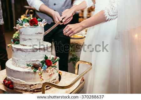 bride and groom cut rustic wedding cake on wedding banquet with red rose and other flowers - stock photo