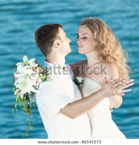 Bride and groom dancing on a rock. - stock photo