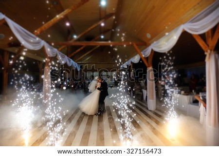 bride and groom dancing on the own wedding with white fume - stock photo