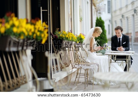 Bride and groom drinking coffee at an outdoor cafe - stock photo