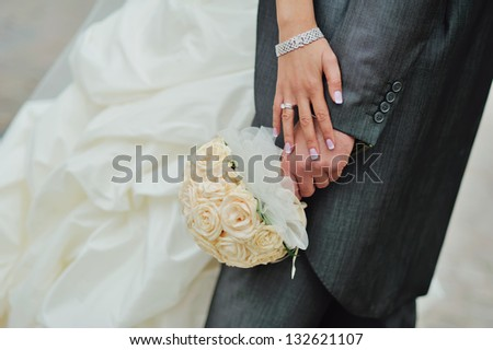 bride and groom embraces, hands - stock photo