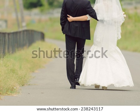bride and groom embracing and walking along road - stock photo