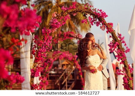 Bride and groom embracing near arch of flowers in Maldives - stock photo