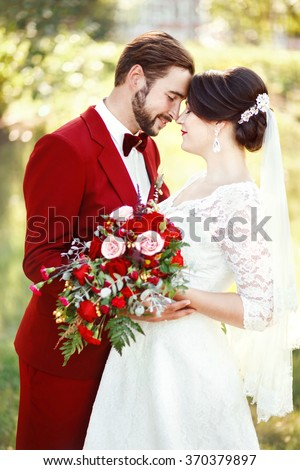 Bride and groom embracing, wedding couple, dark red color marsala style design. Suit with maroon bow tie, white dress, bridal bouquet. Professional makeup. Eternal love, tenderness, beauty concept. - stock photo
