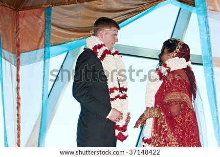 Bride and groom exchange garlands during a traditional hindu ceremony - stock photo