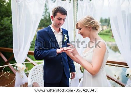 Bride and groom exchange wedding rings and wear at the ceremony. - stock photo