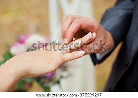 Bride and groom exchanging rings - stock photo