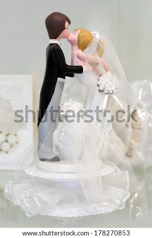 Bride and groom figurines kissing - stock photo