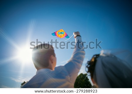 Bride and groom flying a kite together on a wedding day - stock photo