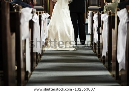 Bride and groom getting married in church view from aisle - stock photo