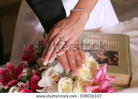 Bride and Groom hands on bible with flowers - stock photo