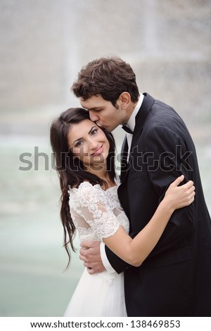 Bride and groom having a romantic moment on their wedding day in Paris - stock photo