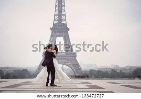 Bride and groom having a romantic moment on their wedding day in Paris, in front of the Eiffel tour - stock photo