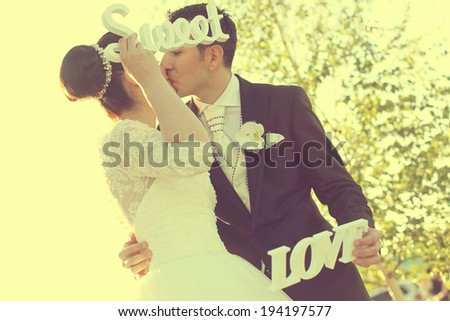 Bride and groom having fun and posing with Sweet Love letters in sunlight  - stock photo