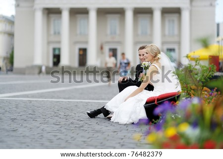 Bride and groom having fun in an old town - stock photo