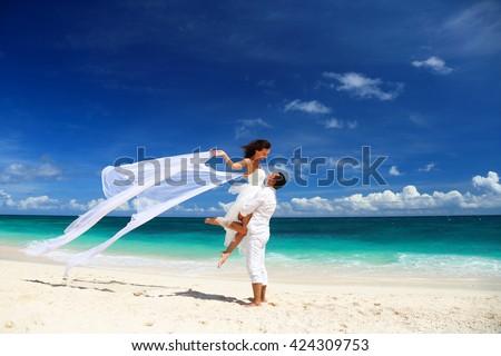Bride and groom having fun on white sandy tropical beach. Beach wedding concept - stock photo