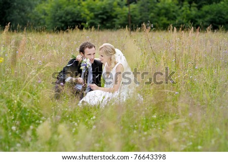 Bride and groom having fun while sitting in a meadow - stock photo