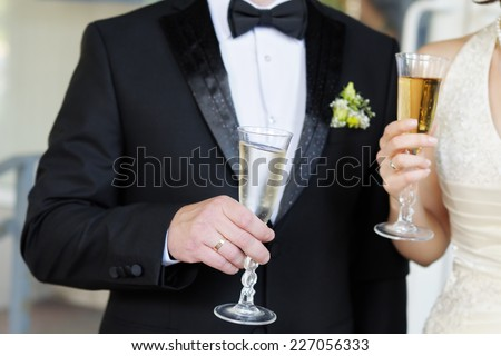 Bride and groom holding champagne glasses  - stock photo