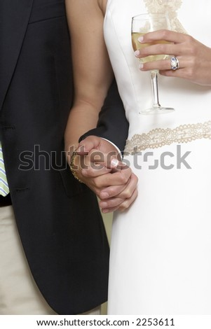 Bride and groom holding hands and a glass of white whine - stock photo