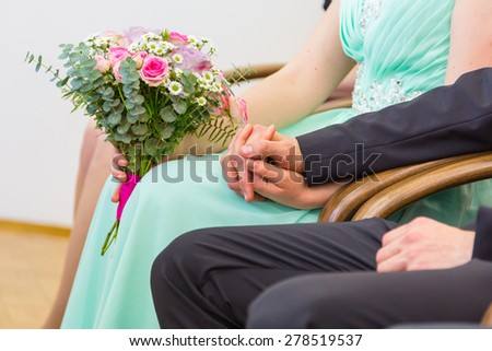 Bride and groom holding hands before the big moment. Wedding ceremony. - stock photo