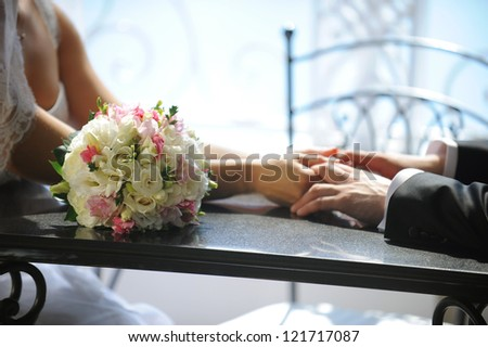 bride and groom holding hands in a cafe - stock photo