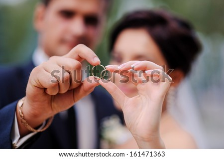 bride and groom holding hands in a ring - stock photo