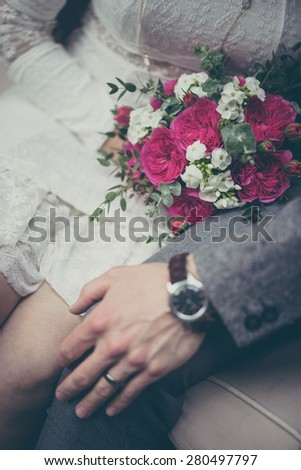 Bride and groom holding hands in vintage pastel colors - stock photo
