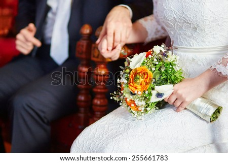 Bride and groom holding hands tenderly during the wedding ceremony, focus on flowers - stock photo