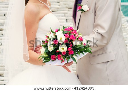 bride and groom holding in her hand a pink bridal bouquet - stock photo