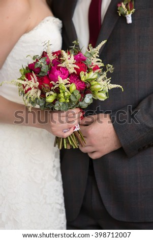 bride and groom holding in her hand a red bridal bouquet - stock photo