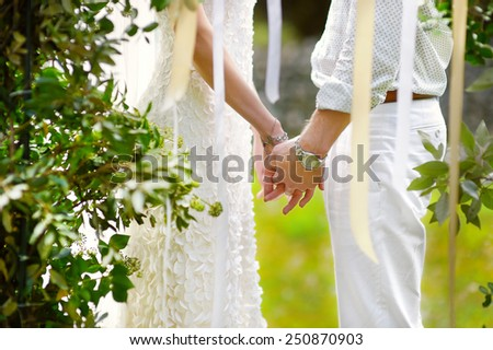 Bride and groom holding their hands during outdoors wedding ceremony - stock photo