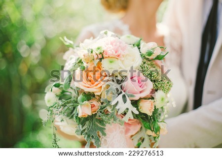bride and groom holding wedding bouquet - stock photo