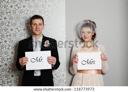 "Bride and groom holding white sheets with the text ""Mr."", ""Mrs."" - stock photo"