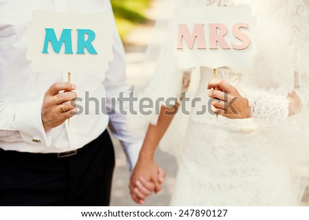 bride and groom holding wooden signs - stock photo