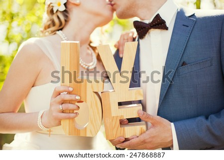 bride and groom holding wooden word love - stock photo