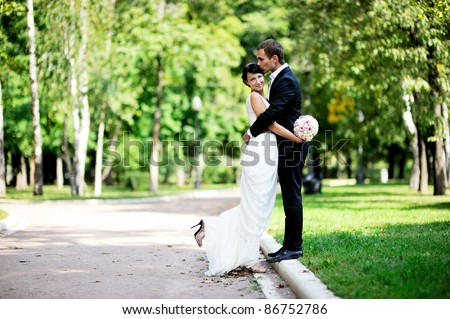Bride and groom hugging each other gently during a walk in the summer park - stock photo